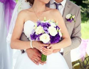 Happy bride and groom on their wedding. Wedding couple bride and groom holding hands. Wedding bouquet closeup.